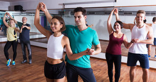 Dancing couples learning salsa. Positive dancing couples learning salsa at dance class royalty free stock photography