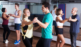 Dancing couples learning salsa Royalty Free Stock Image