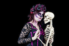 Dancing With The Dead. Day of The Dead. A woman dressed as a sugar skull dancing with the skeleton of a departed love one Stock Image