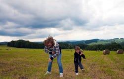 Dancing del ragazzo e della ragazza sul campo falciato in un covone Immagini Stock