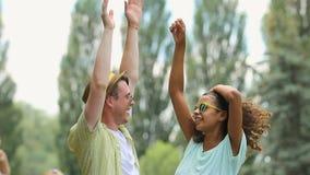Dancing della donna e del giovane al fest all'aperto di musica con la loro mano su nell'aria archivi video