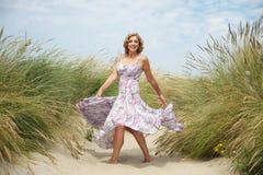 Dancing della donna nella sabbia alla spiaggia Fotografie Stock