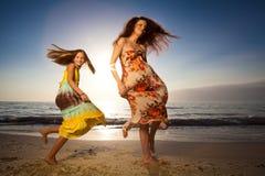 Dancing della figlia e della madre sulla bella spiaggia. fotografia stock