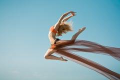 Dancing della ragazza con il grande panno arancione Fotografia Stock