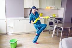 Dancing divertente del lavoratore nella cucina Finge il gioco sulla chitarra Ma la ragazza ha zazzera in mani nel supporto di que fotografia stock libera da diritti