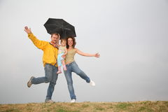 Dancing family under umbrella. Family with the umbrella against gray sky Royalty Free Stock Photography