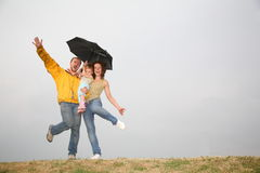 Dancing family under umbrella. Family with the umbrella against gray sky Stock Image