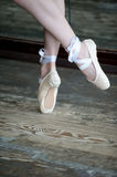 Dancing feet in ballet shoes on wooden floor Stock Image