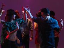 Dancing felice dei giovani nel randello di notte Immagini Stock