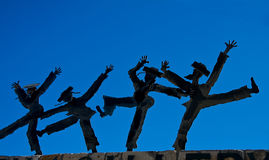 Dancing figurines against blue sky. Dancing figurines of masked men in Jewish orthodox outfits against blue skies Royalty Free Stock Photography