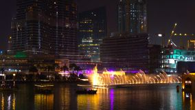 The Dancing Fountain of Dubai performs to the beat of the music at night show on lake area. stock image