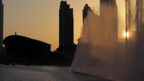 Dancing fountains in Dubai. Dubai fountain near Burj Khalifa illuminated by the city at sunset stock video