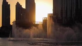 Dancing fountains at sunset in Dubai. Dubai fountain near Burj Khalifa illuminated by the city at sunset stock footage