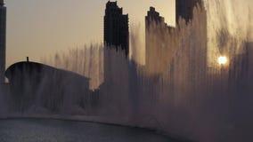 Dancing fountains during sunset in Dubai. Dubai fountain near Burj Khalifa illuminated by the city at sunset stock video