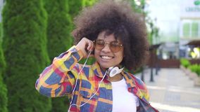 Dancing fun african american woman with an afro hairstyle on the street close up slow mo. Dancing fun african american woman with an afro hairstyle in shirt and stock video