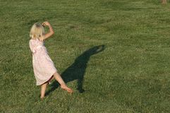Dancing girl. A young girl watches her shadow as she dances on a summer afternoon Stock Photography