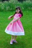 Dancing Girl. Dancing young brunette child wearing a pink and white dress, in a grassy meadow Royalty Free Stock Photos