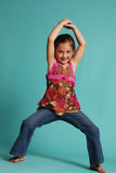 Dancing girl. Cute young girl dancing in jeans and a flowered shirt Royalty Free Stock Photo