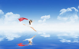 Dancing girl above water surface Stock Photos