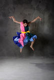 Dancing girl in colorful dress on the dirty grunge Royalty Free Stock Image