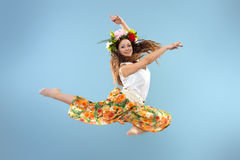 Dancing girl. In colorful traditional dress, on a blue background Royalty Free Stock Photo