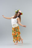 Dancing girl. In colorful traditional dress, on a gray background Royalty Free Stock Photography