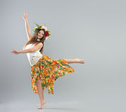 Dancing girl. In colorful traditional dress, on a gray background Stock Images