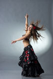 Dancing girl. In a dark traditional dress Stock Photography