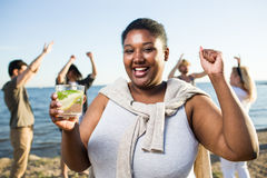 Summer energy. Dancing girl with drink enjoying beach party with her friends Royalty Free Stock Photos