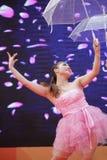 Dancing girl performing umbrella dance Stock Images