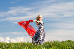Dancing girl with red scarf, copy. Dancing girl with red scarf on meadow in spring. Copy space stock photo