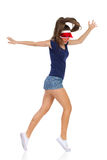 Dancing Girl Tip Toe. Woman in blue shirt, jeans shorts white sneakers and red sun visor cap dancing tip toe. Full length studio shot on white royalty free stock photography
