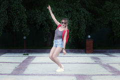 A dancing girl wearing glasses, denim shorts, gray shirt with backpack. Royalty Free Stock Photos