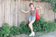 A dancing girl wearing glasses, denim shorts, gray shirt with backpack Royalty Free Stock Photo