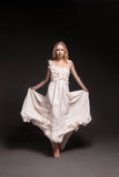 Dancing girl in wedding dress over dark background Stock Image