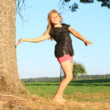Dancing girl. Young girl - barefoot kid in black t-shirt and pink shorts dancing by trunk of tree Stock Images