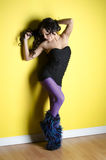 Dancing girl. Young raver girl dancing on a yellow wall Royalty Free Stock Image