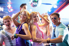 Dancing girls. Portrait of cheerful girls dancing at party with happy friends near by Stock Photo