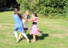 Dancing girls. Three happy little girls in colorful dresses dancing and twisting on green meadow Stock Photography