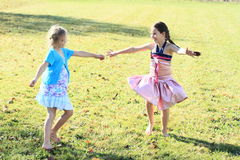 Dancing girls. Two happy little girls in dresses dancing and twisting on green meadow Royalty Free Stock Photos