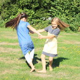 Dancing girls. Two happy little girls in dresses dancing and twisting on green meadow with flying hair Royalty Free Stock Photo