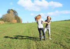 Dancing girls. Two happy little girls dancing and twisting on green meadow with blue sky behind Royalty Free Stock Images