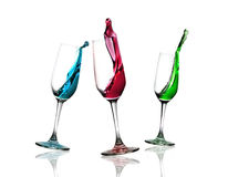 Dancing Glasses. Glasses with red, green, blue drink dancing and splashing water playfully Stock Photo