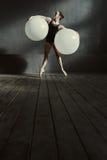 Dancing grazioso della ginnasta facendo uso delle palle bianche Fotografie Stock