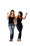 Dancing groovy teenager girls. Beautiful fun happy smiling young women teenager girls dancing groovy, wearing black tank top and blue denim jeans, isolated Stock Photos