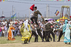 Dancing group in folk costumes and the form of the Soviet army at the festival Sabantui-2014 Royalty Free Stock Photo