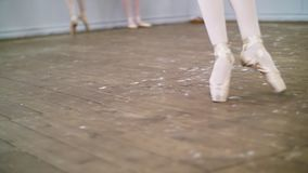 In dancing hall, Young ballerina in black leotard performs glissade en tournant, She moving through the ballet class. Elegantly stock video