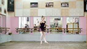 In dancing hall, Young ballerina in black leotard performs pas courru , pointe , She is moving through the ballet class. Elegantly stock footage