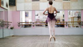 In dancing hall, Young ballerina in black leotard performs tour chaines, She moving through the ballet class elegantly,. In dancing hall, Young ballerina in stock video