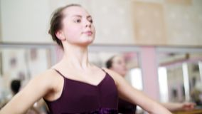 In dancing hall, Young ballerina in purple leotard performs a certain ballet exercise, first position of hands,. In dancing hall, Young ballerina in purple stock video footage